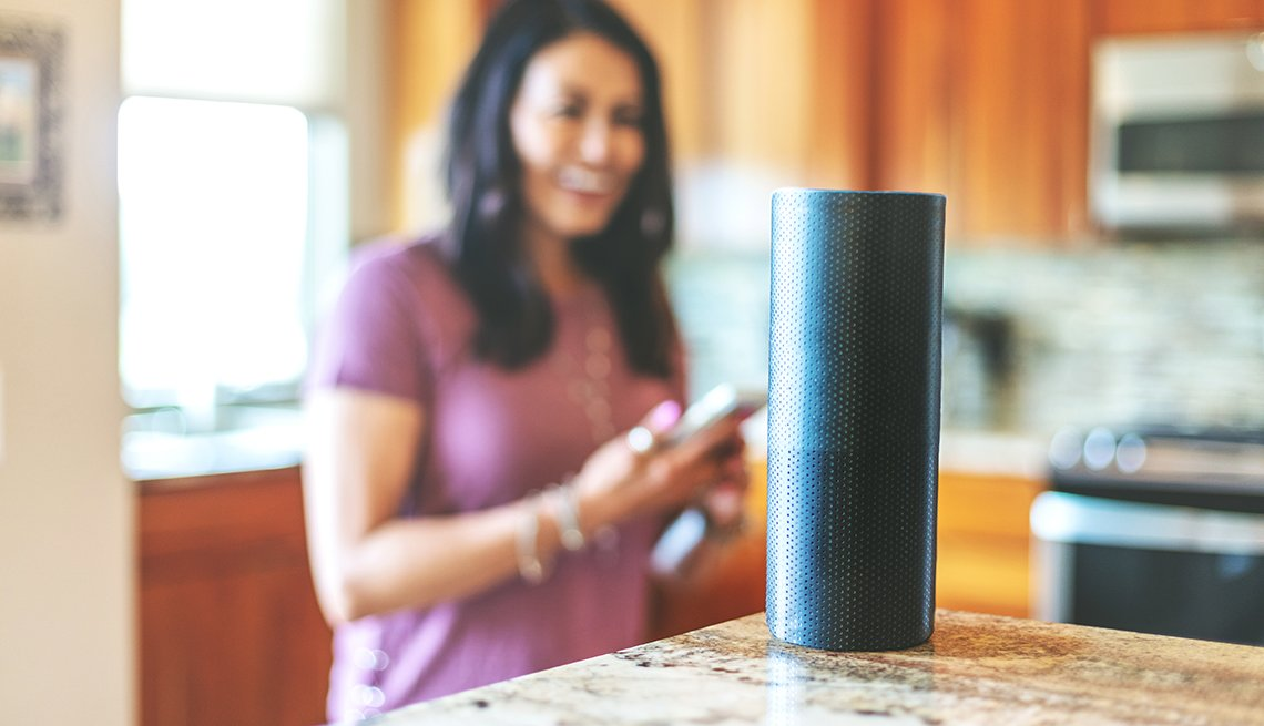 Mujer en la cocina sostiene su teléfono frente a un dispositivo de altavoz inteligente