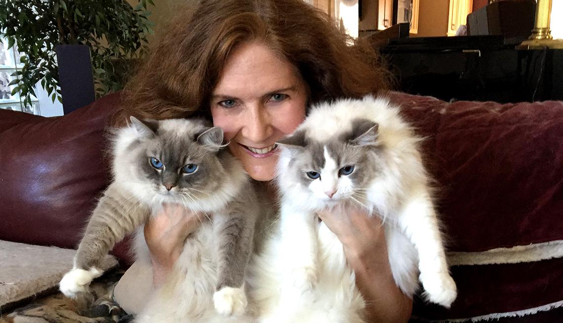 Mujer sostiene dos gatos junto a su cara