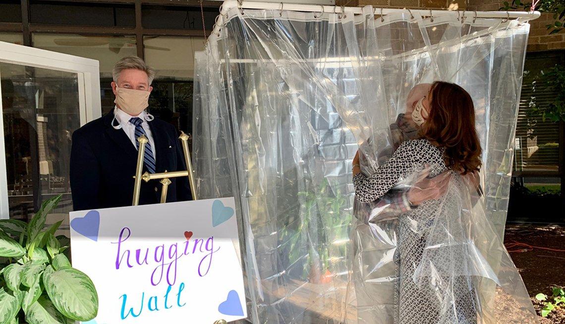 Un anciano se abraza con un visitante a través de una cortina de plástico