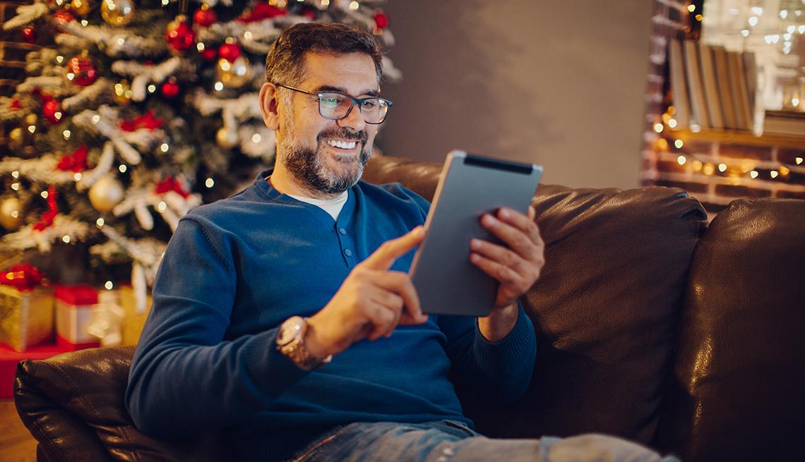 Hombre sentado frente a tableta con un árbol de Navidad de fondo