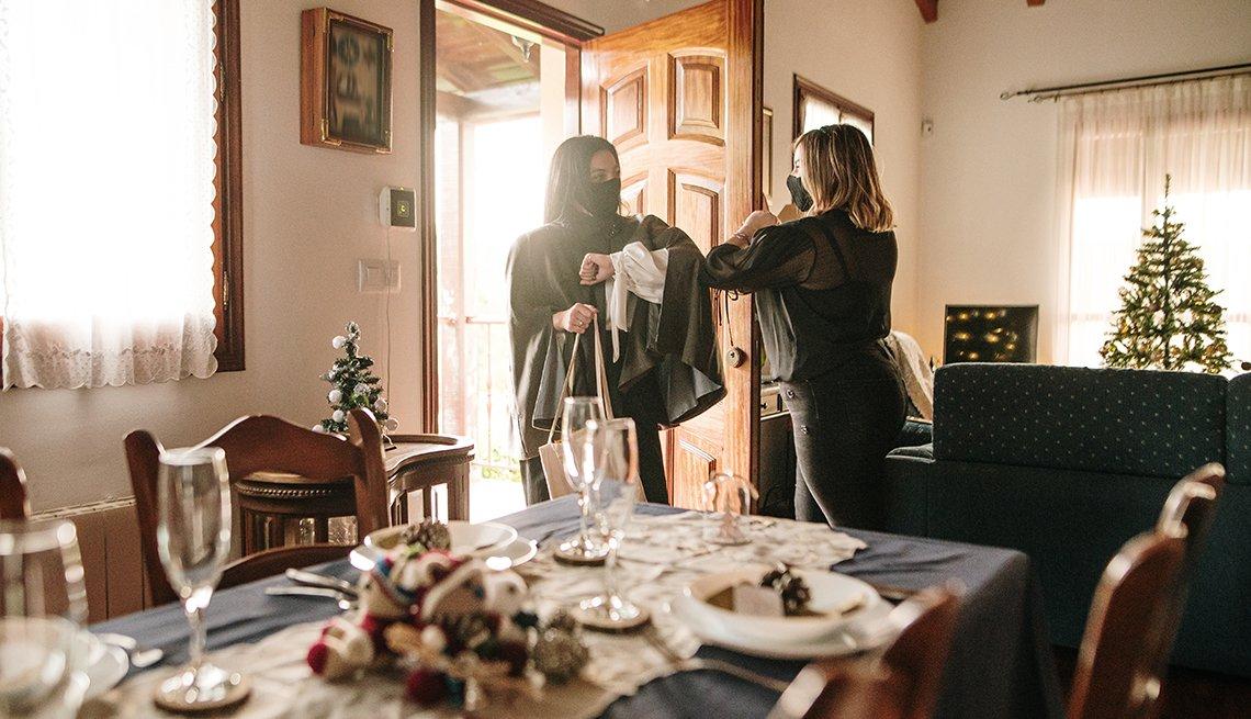 Dos mujeres se saludan en la entrada de una casa, con una mesa decorada de Navidad para cenar