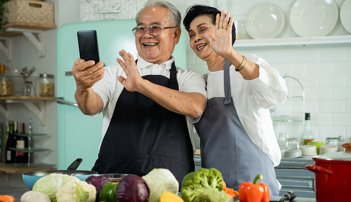 A man and woman stand in a kitchen waving at a phone