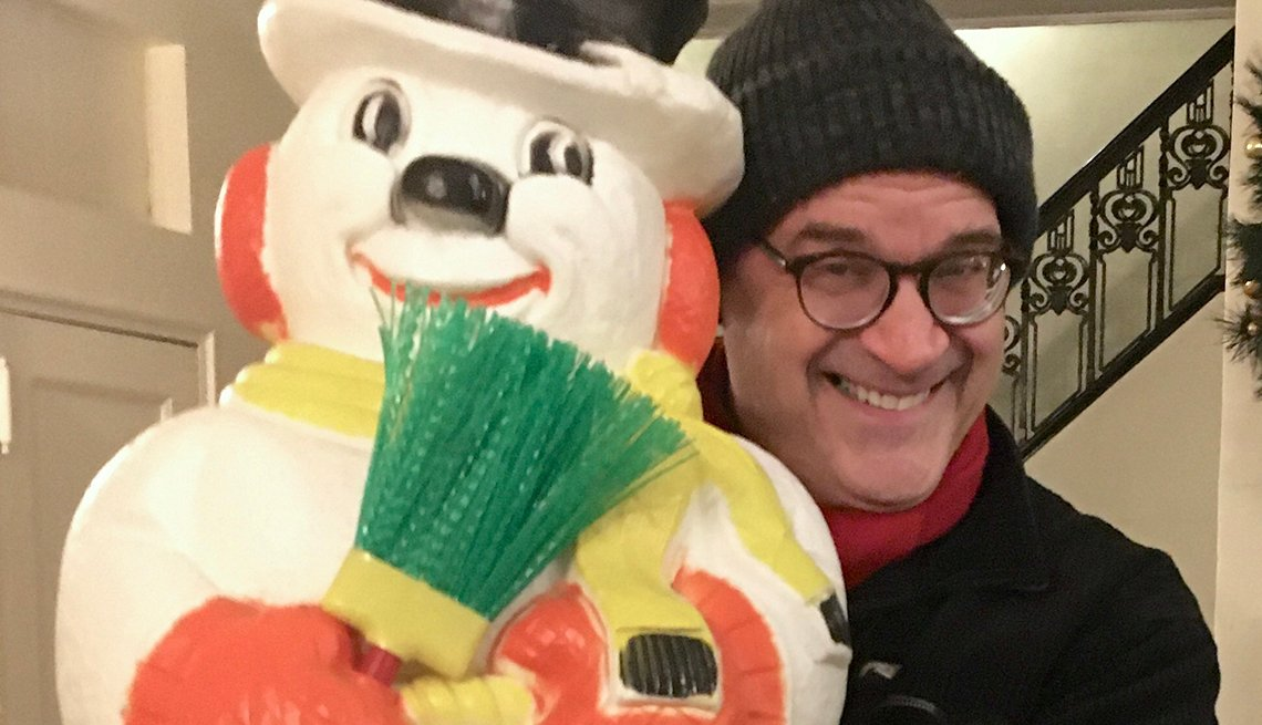 Man holding a snowman and smiling