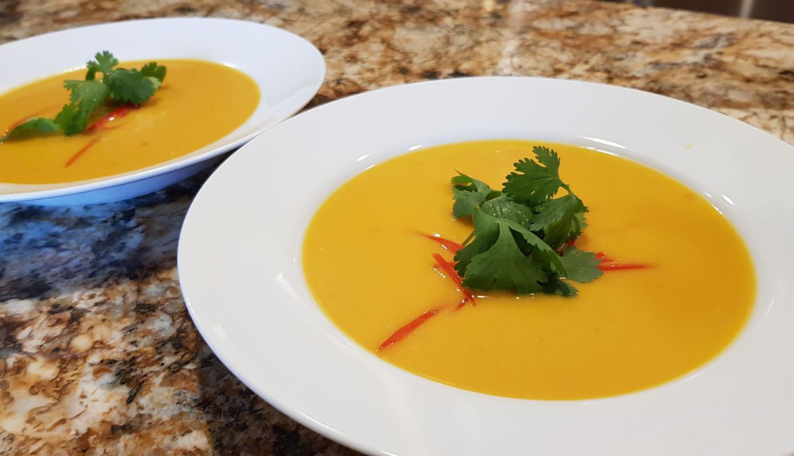 Dos platos servidos con sopa de calabaza