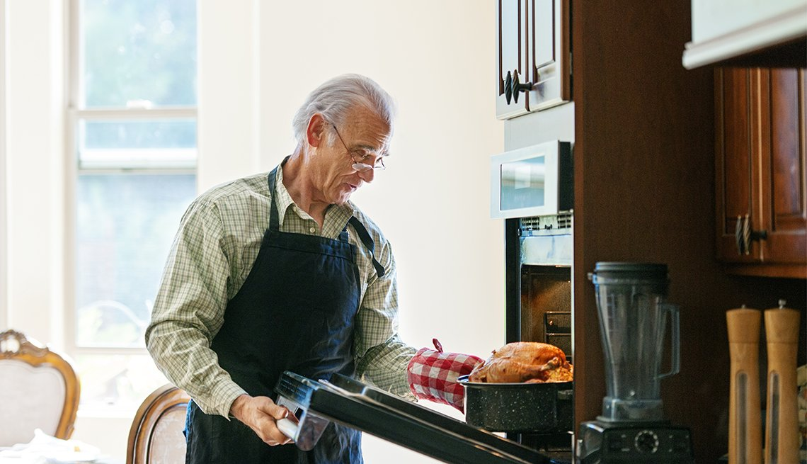 Hombre mayor cocinando la cena para el Día de Acción de Gracias
