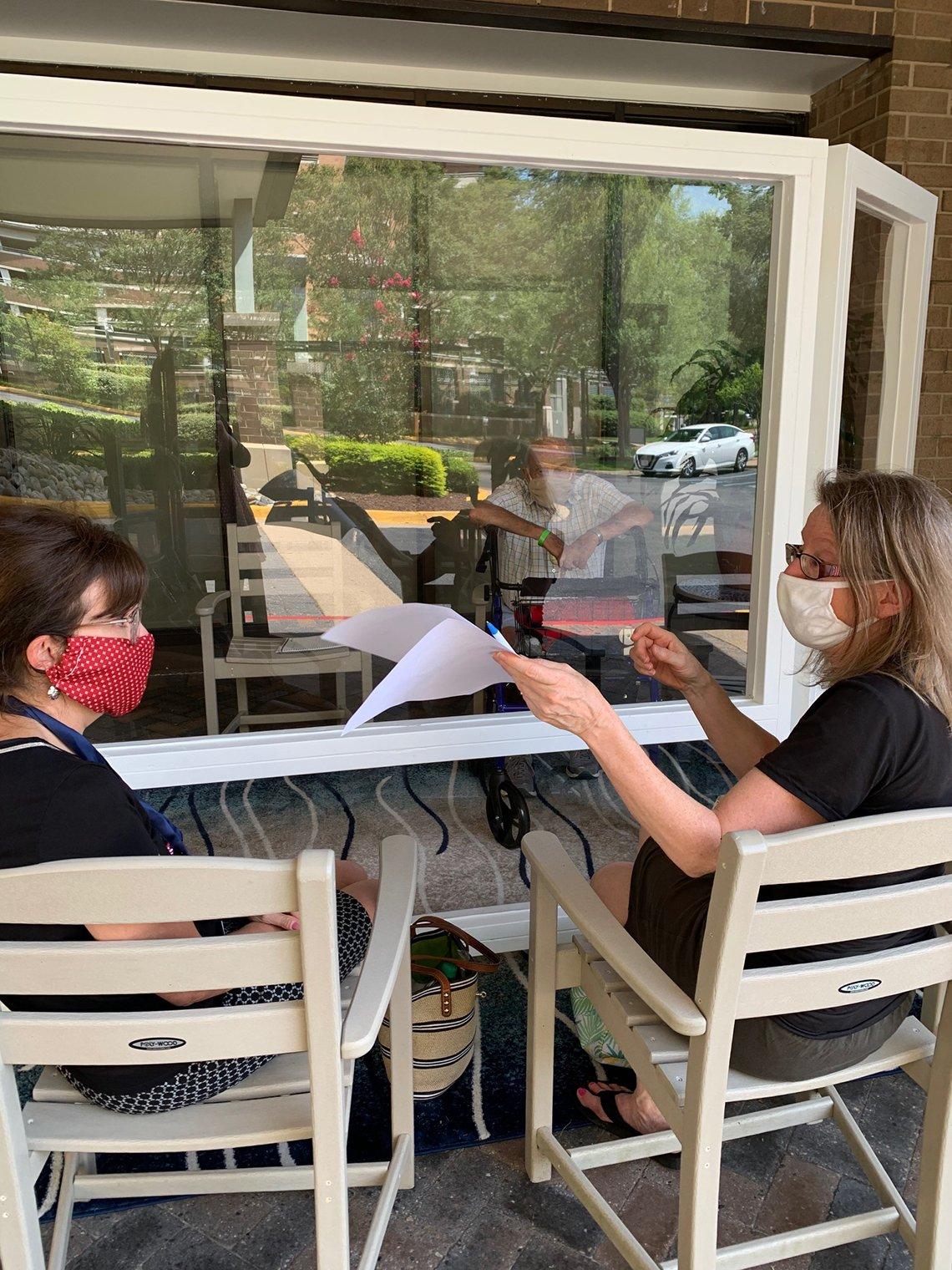 Dos mujeres sentadas en la parte exterior de un restaurante