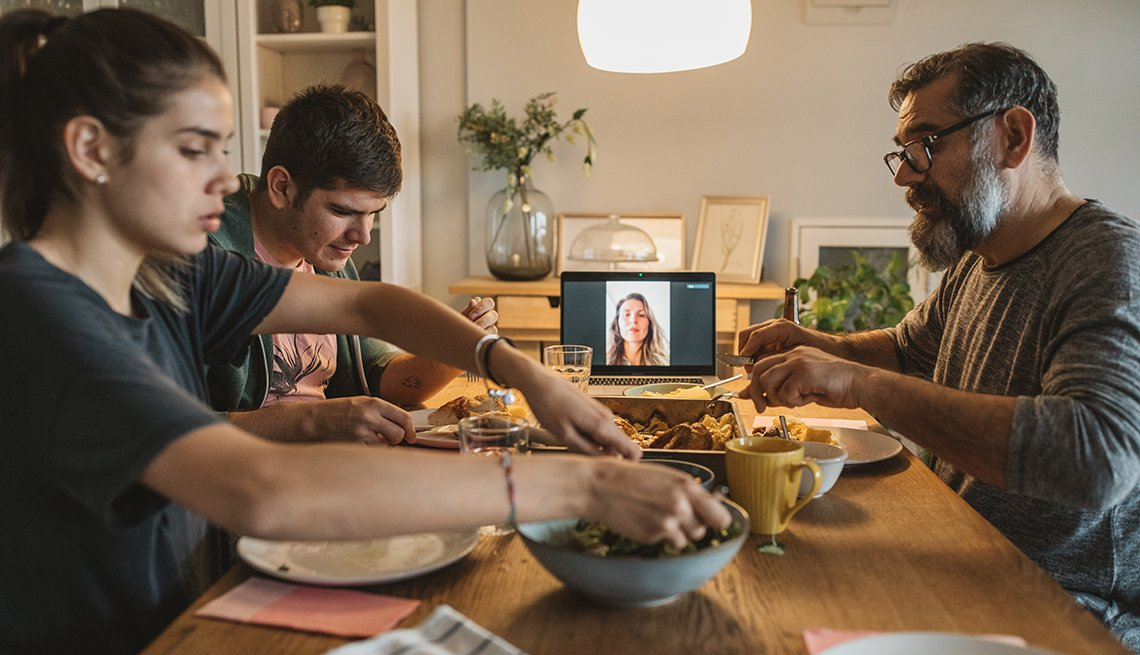 Family having dinner with mother on a tablet screen