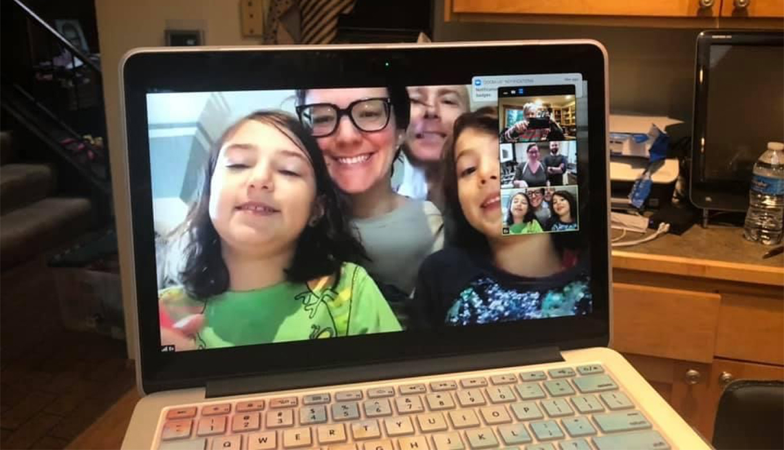 A family on a video chat via a laptop