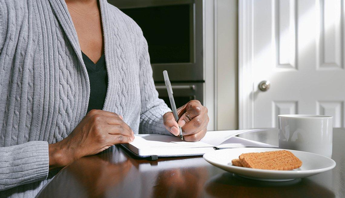 Primer plano de una mujer escribiendo en su diario