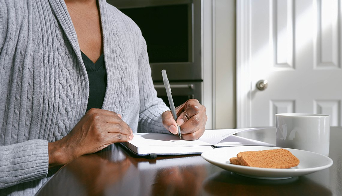 Close-up of unrecognizable woman writing in journal at kitchen table