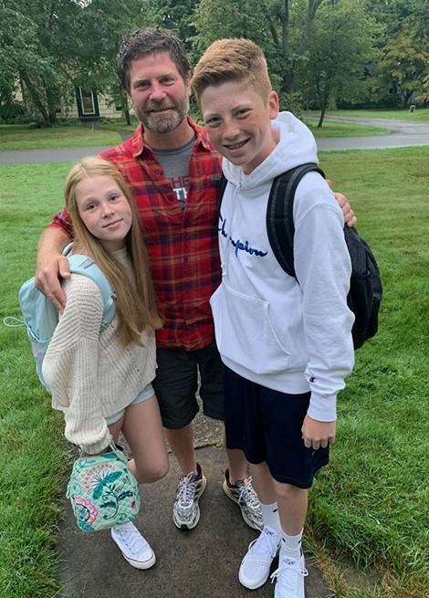 Un hombre posa para la foto junto a sus dos hijos