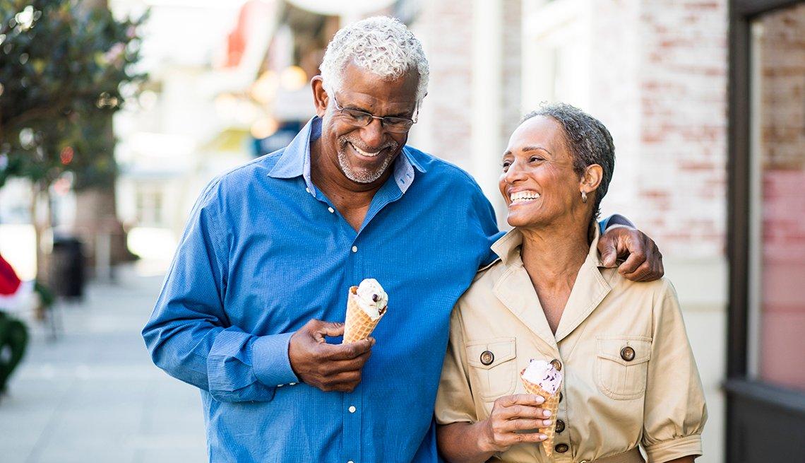 Una pareja madura disfruta de un helado cuando camina por la calle