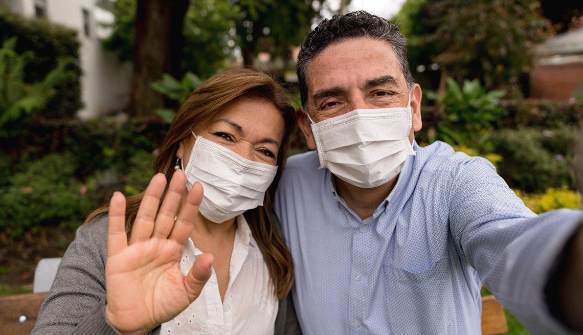 Pareja posando para una foto, mientras llevan puesta una mascarilla quirúrgica al aire libre