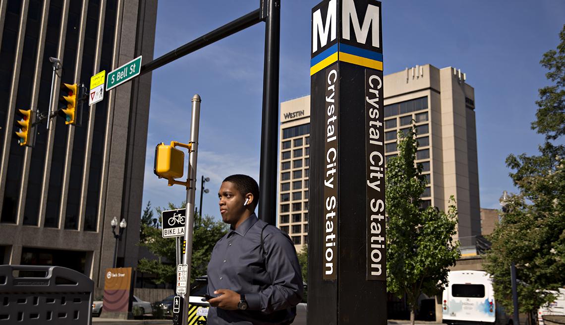 Un peatón pasa junto a un letrero de la estación de metro de Crystal City