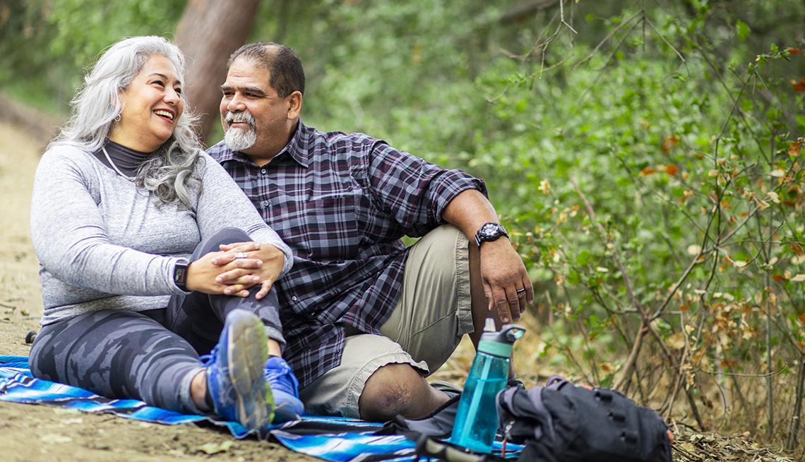 Una pareja disfrutando de un picnic sobre una manta en el bosque