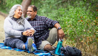 A couple enjoying a picnic on a blanket in the woods.