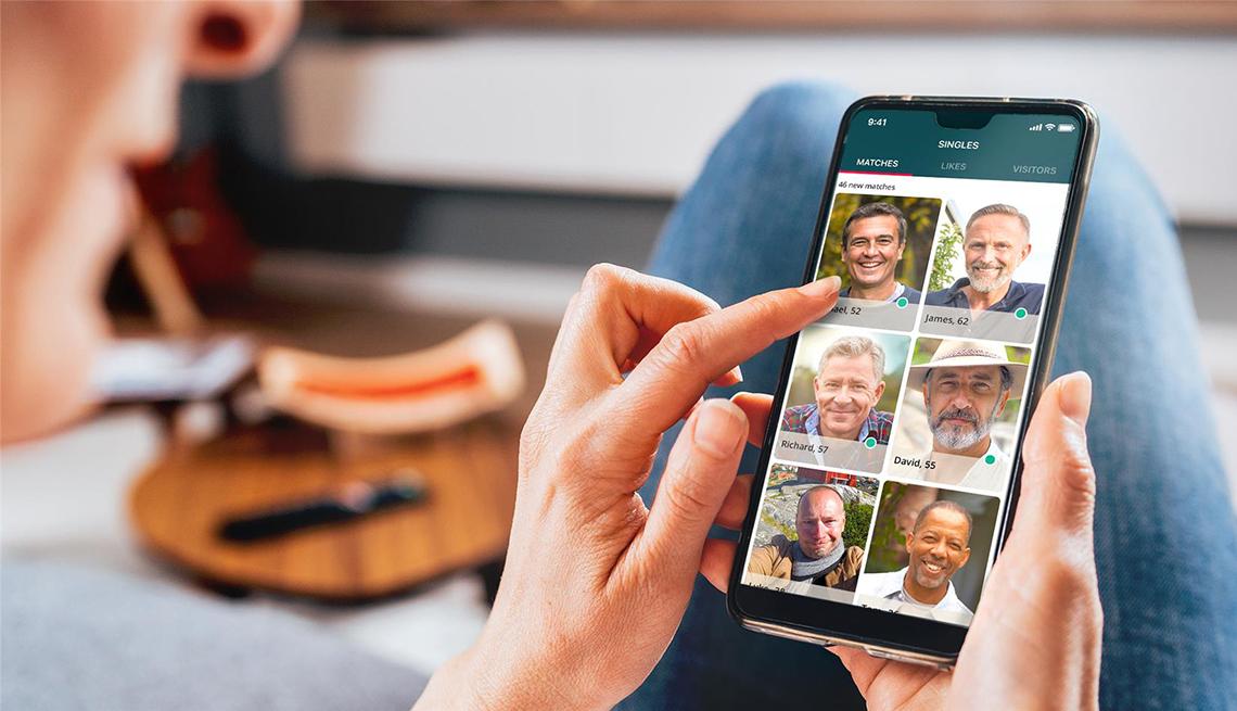 Una mujer en una aplicación de citas mirando perfiles de hombres en su teléfono inteligente