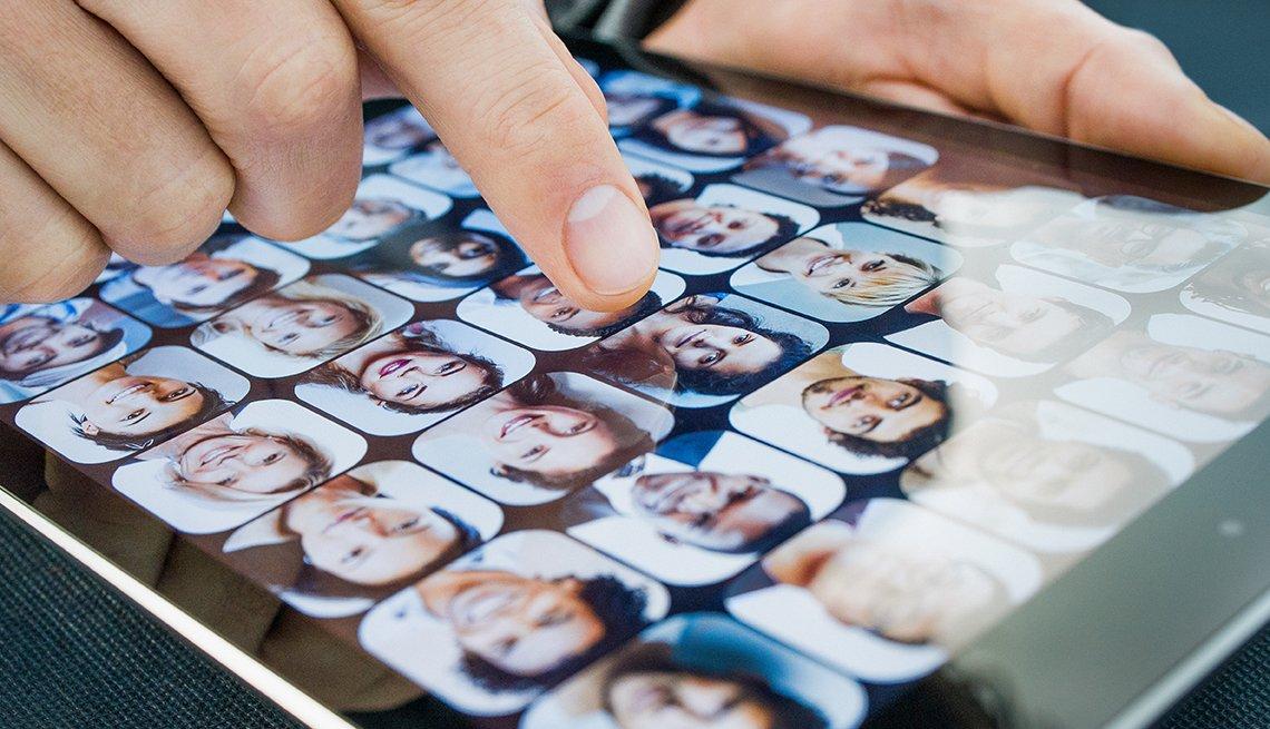 Un dedo toca una tableta con múltiples caras de hombres