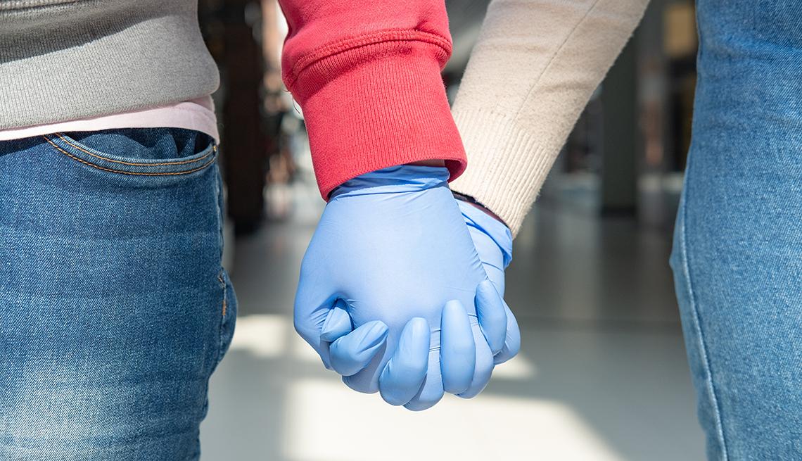 Dos personas tomadas de la mano con guantes