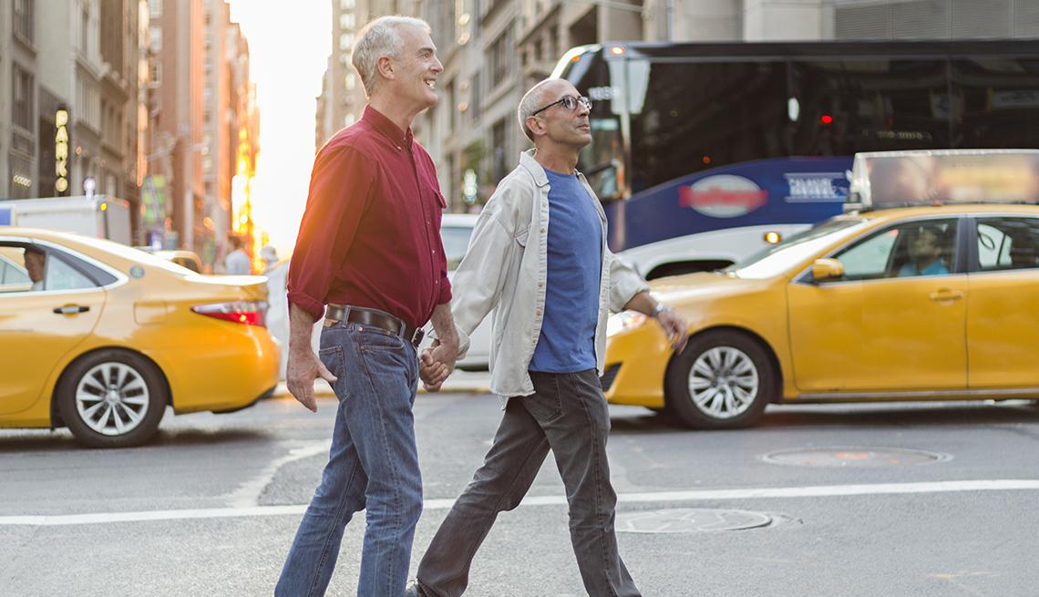 Pareja masculina tomada de la mano cuando cruza una calle