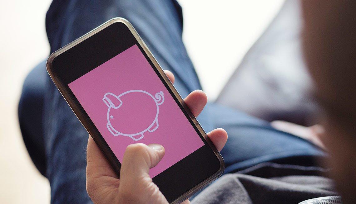 Hombre sostiene un teléfono inteligente con la imagen de un cochino en la pantalla