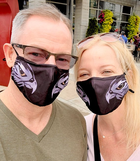 Grayce and Bradd wearing face masks smile for a photo
