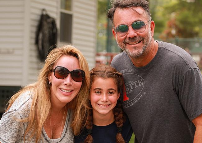 Valerie Zucker sonríe junto a una niña y un hombre
