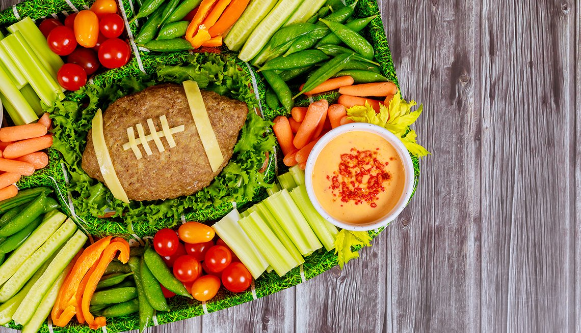 Football meatloaf with fresh vegetable platter and dipping for championship game fan party.