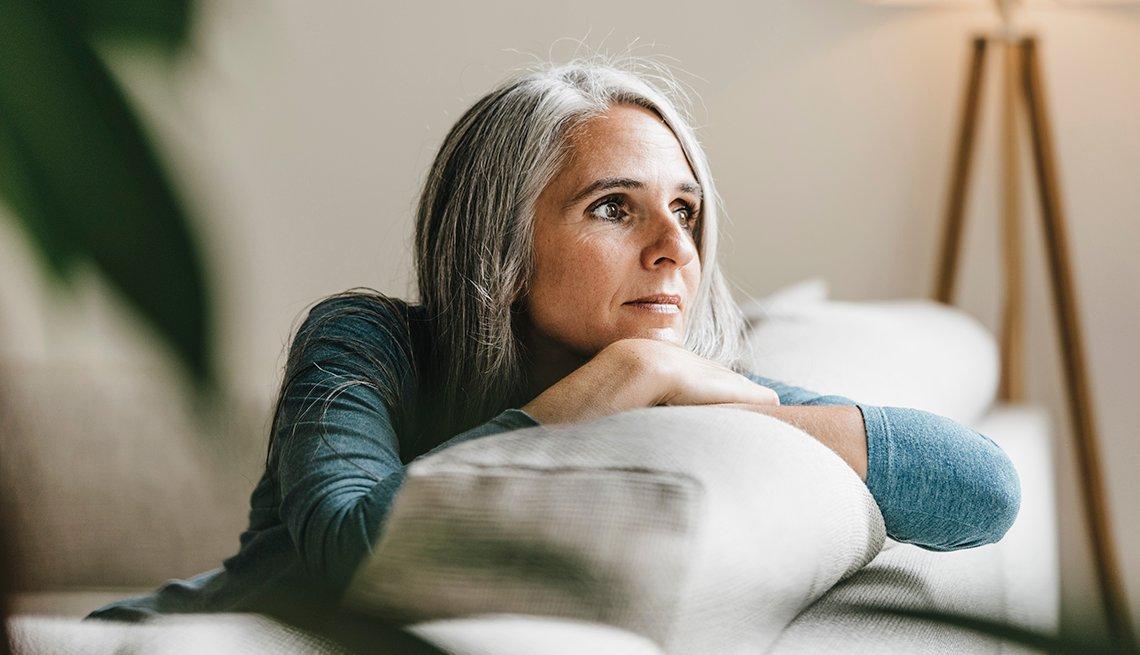 Una mujer mirando por una ventana mientras está sentada en su sofá