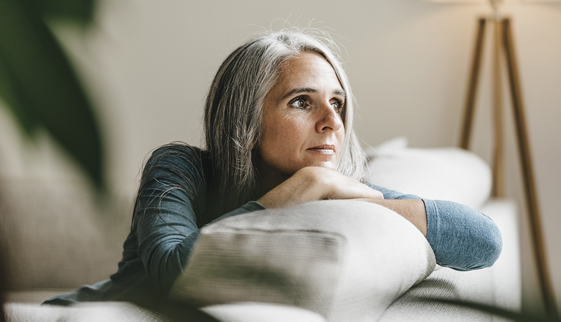 A woman looking outside a window while sitting on her couch