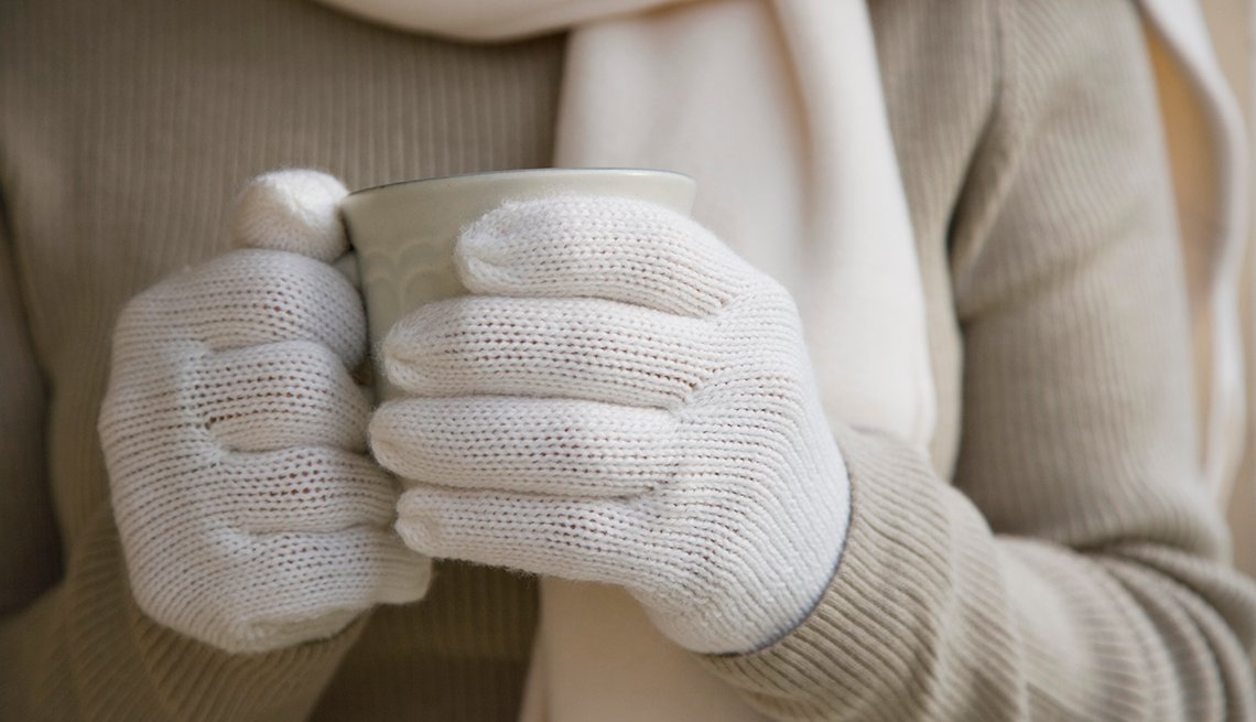 Mujer sosteniendo una taza con guantes, bufanda y abrigo