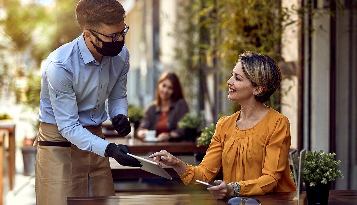Mujer habla con un mesero en un restaurante