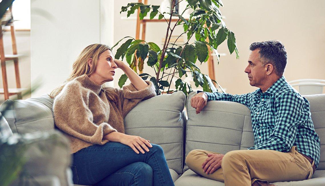 Pareja discute mientras están sentados en un sofá