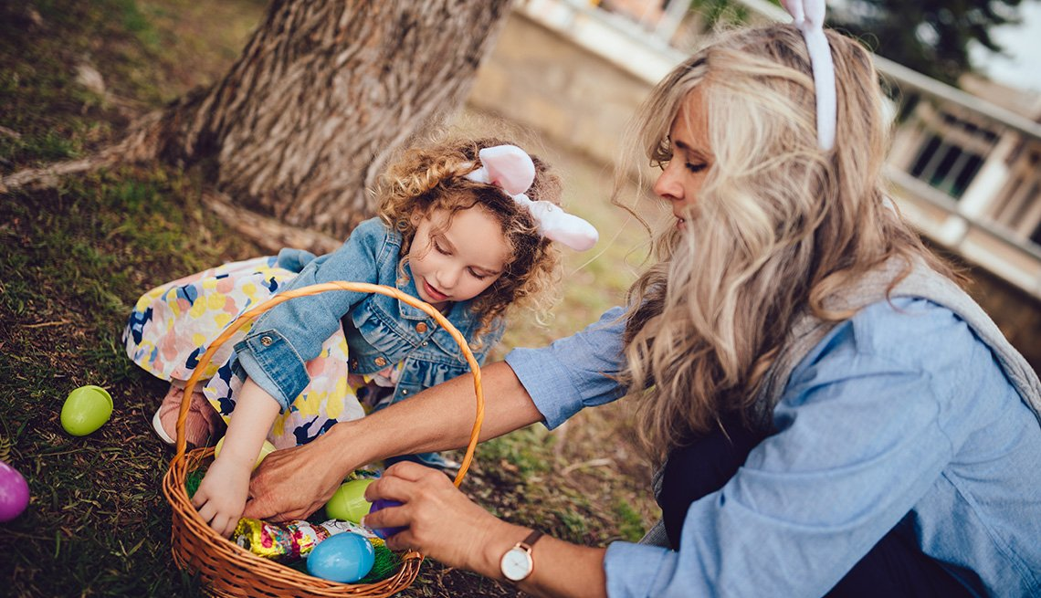 Grandmother and little granddaughter having fun in garden collecting eggs during Easter Egg hunt