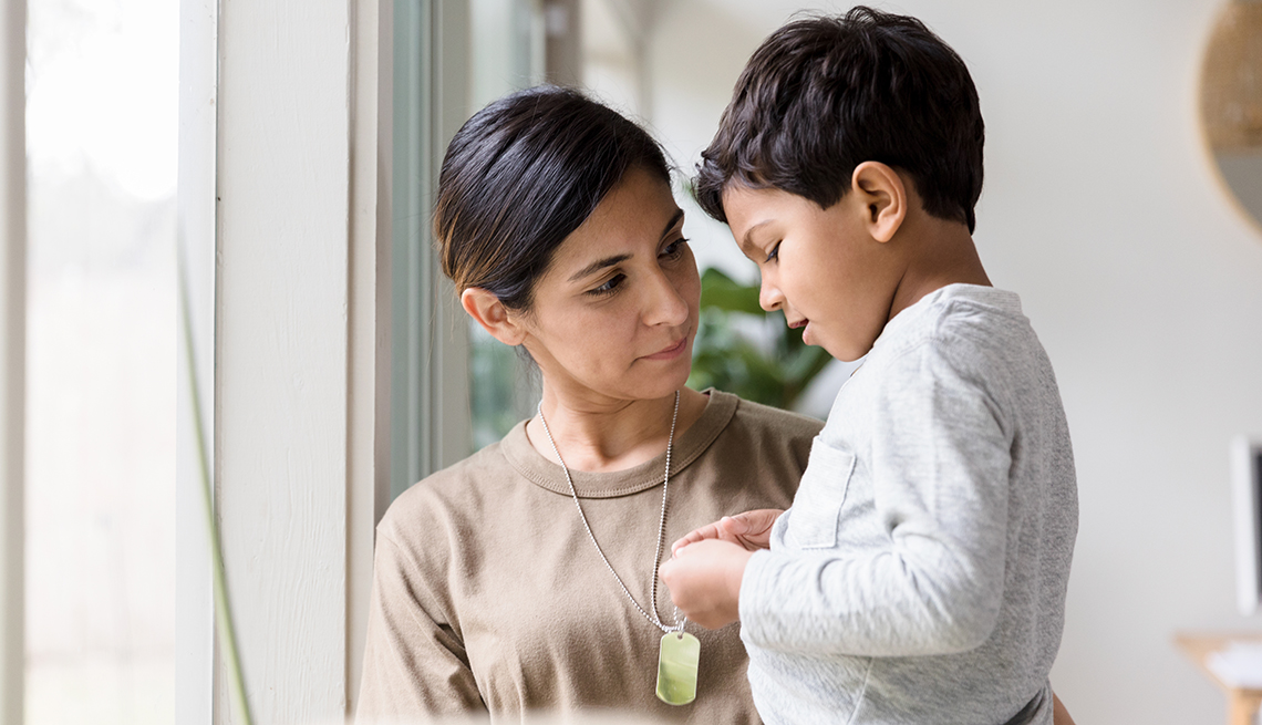 A woman is standing by a window holding a child
