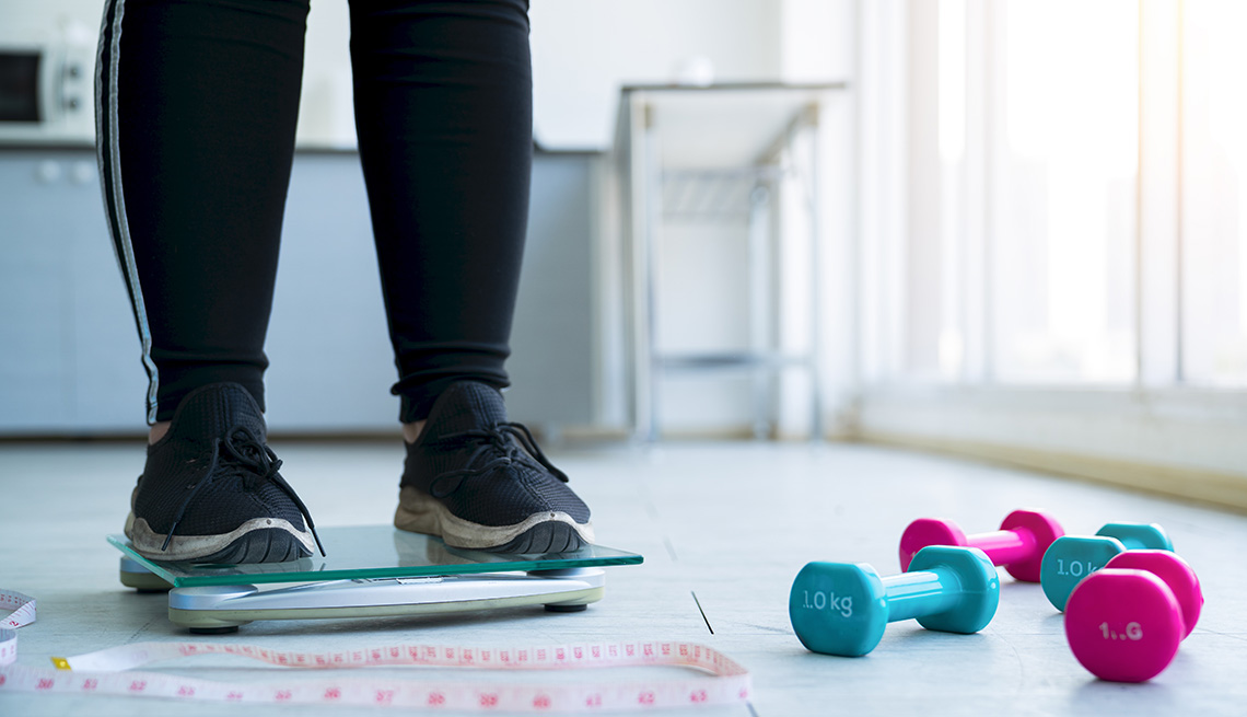 Close up legs of overweight woman checking her weight scales and drumbell, tape measure beside her.