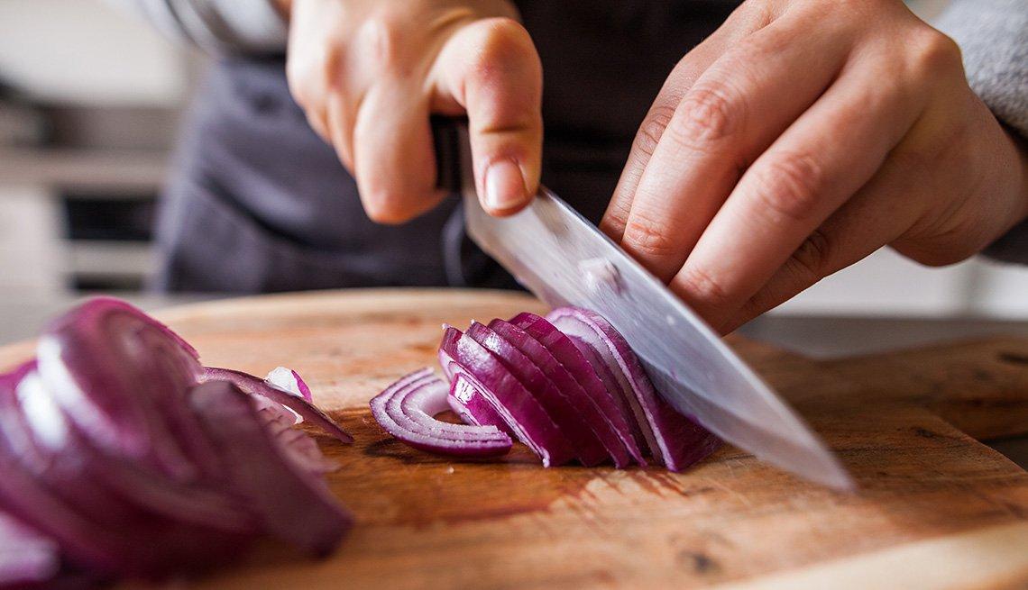 Persona corta una cebolla