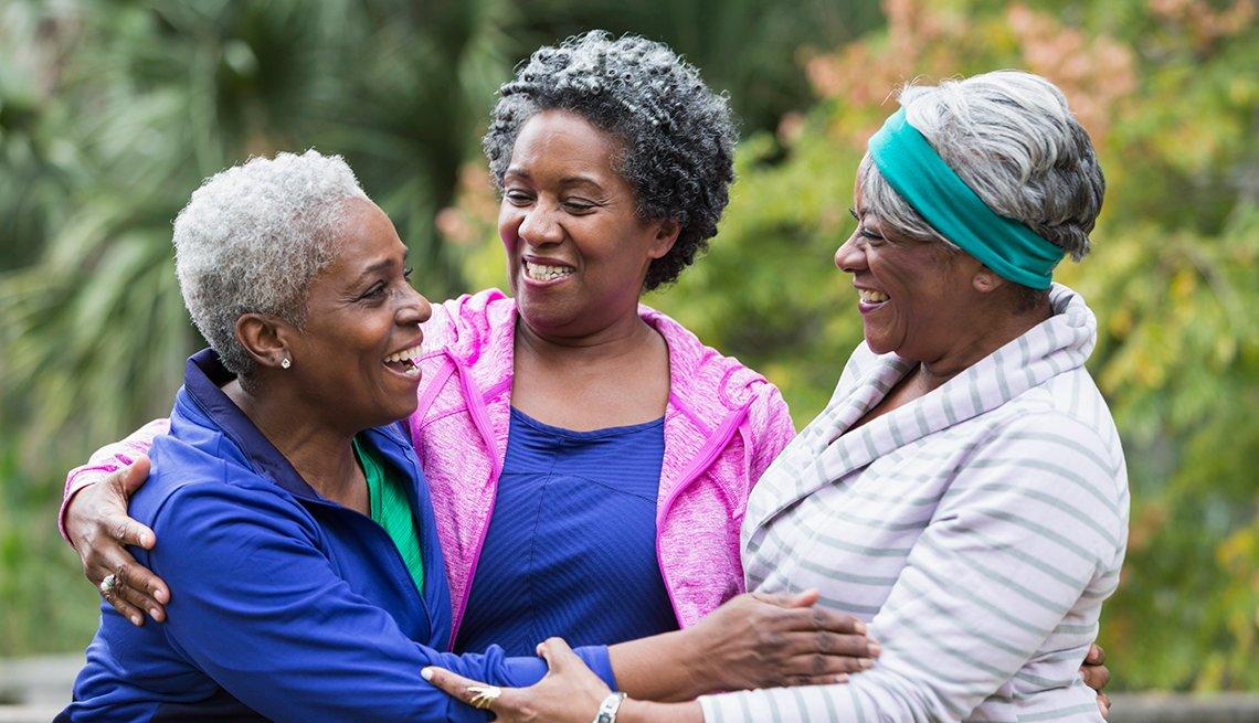 3 mujeres sonríen mientras están en un espacio exterior