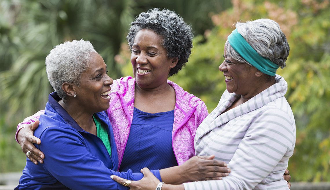 A group of three women standing together at the park, smiling, laughing and talking.