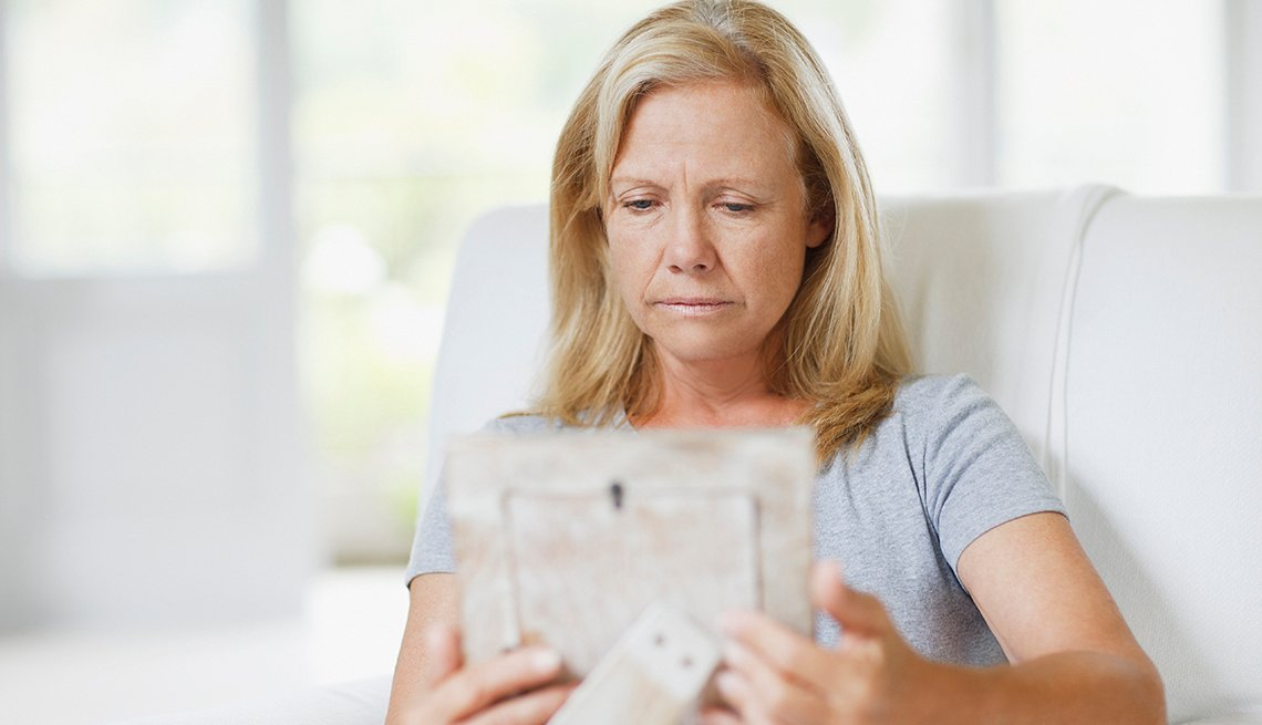 Sad woman, looking at a photo, grieving