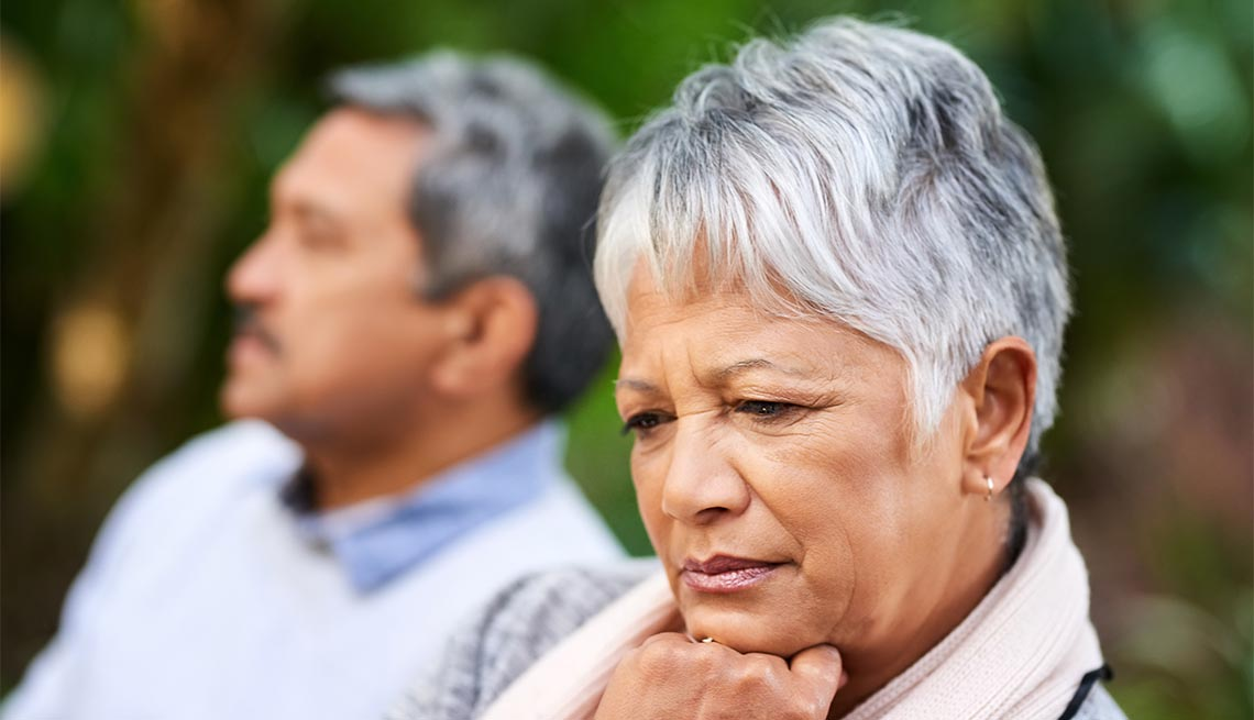 woman looking upset with her husband in the background