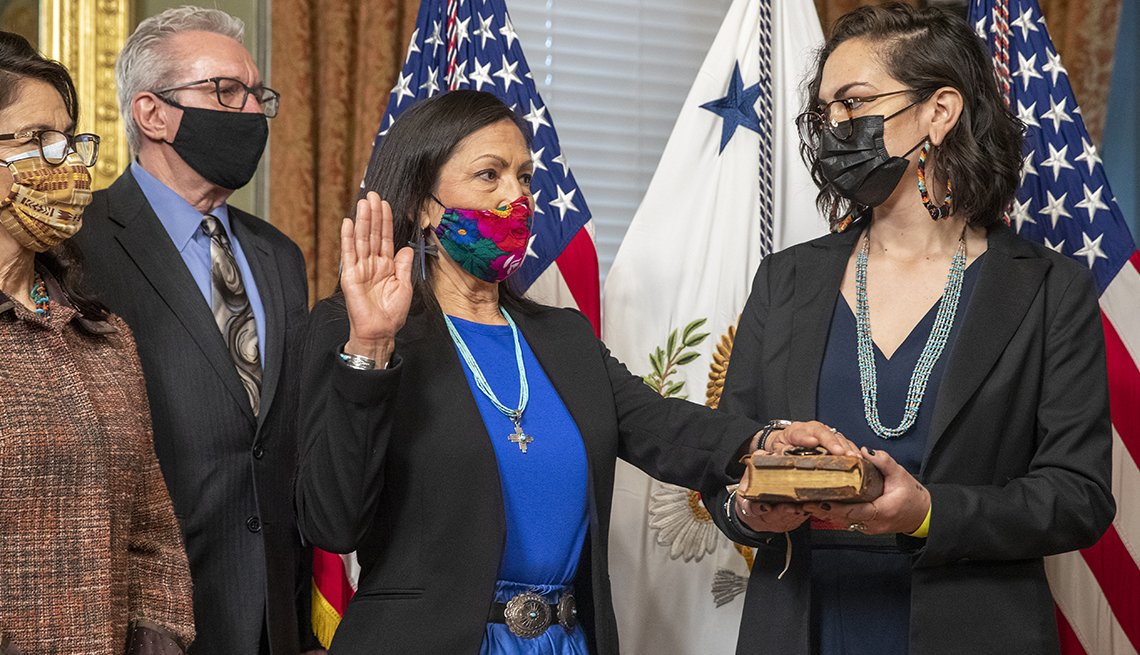 Deb Haaland, U.S. secretary of the interior, second left, reacts during a swearing in ceremon