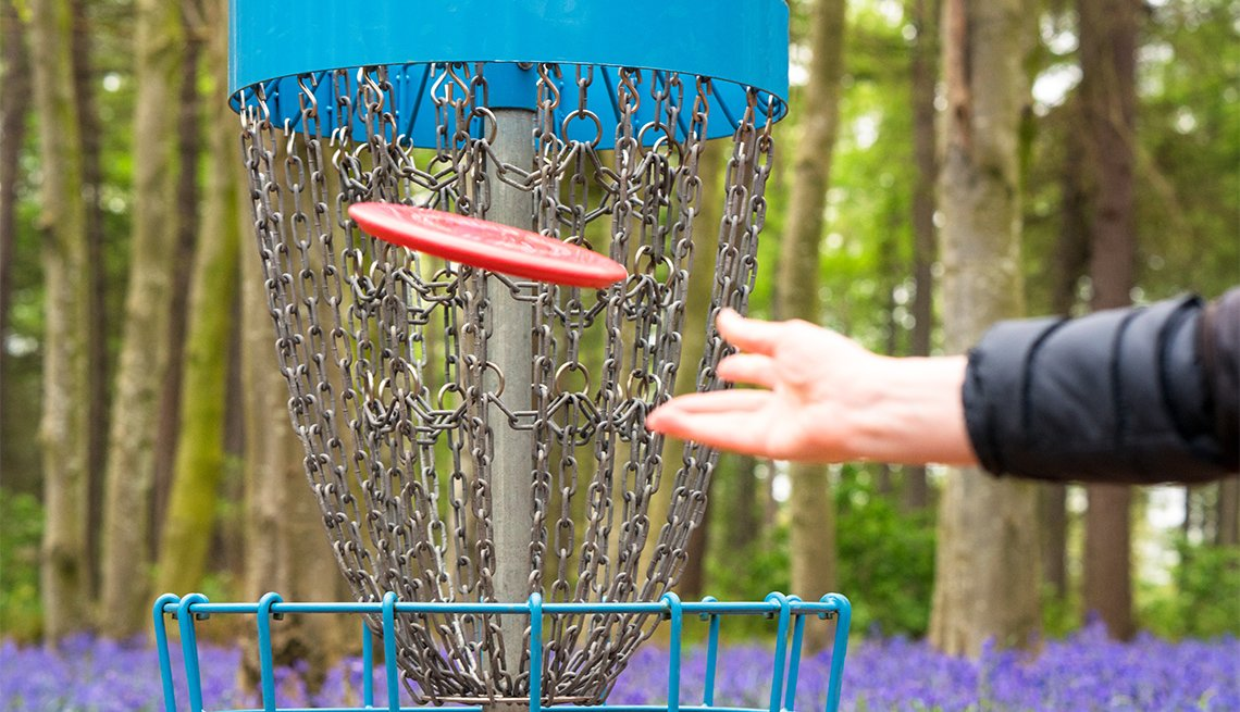 a player throwing a red disc at short range towards the basket
