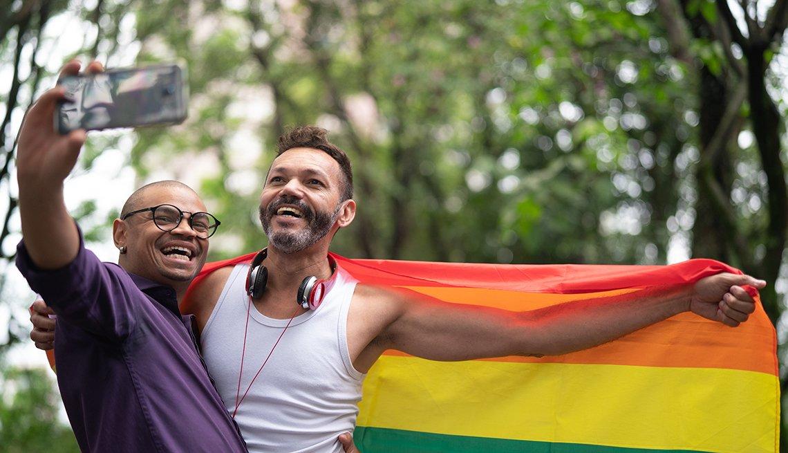 Dos hombres sosteniendo una bandera del arco iris, tomando una foto