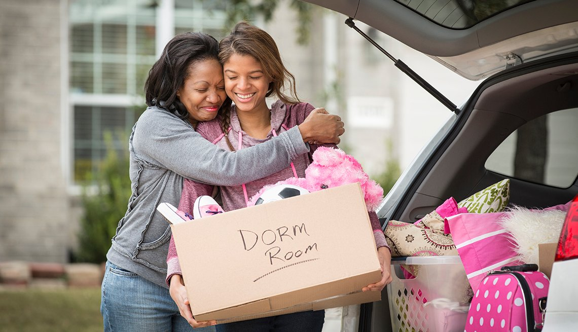 A young adult loading a box that says dorm room on it into her car as her mother hugs her
