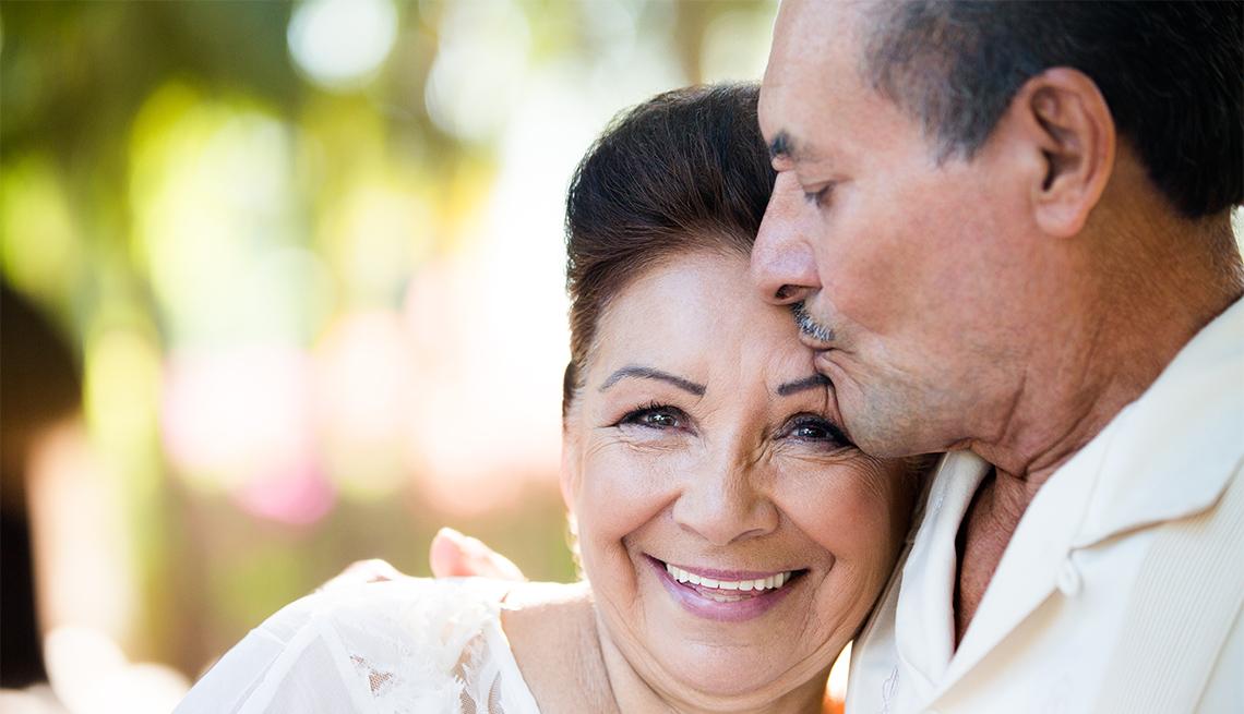 Un hombre y una mujer lucen felices mientras el hombre besa la frente de la mujer