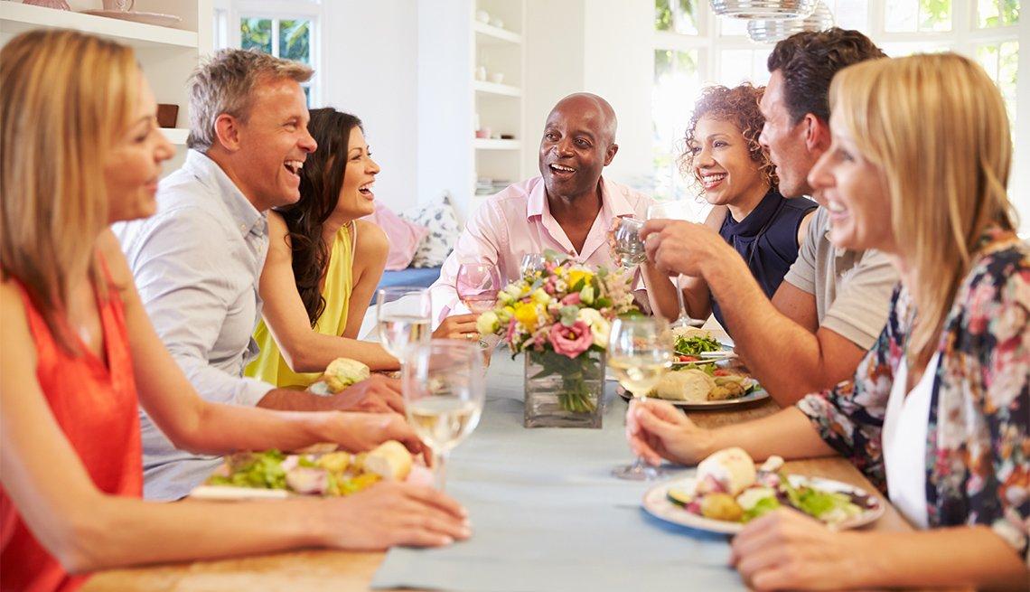 Grupo de amigos sentados alrededor de la mesa mientras cenan