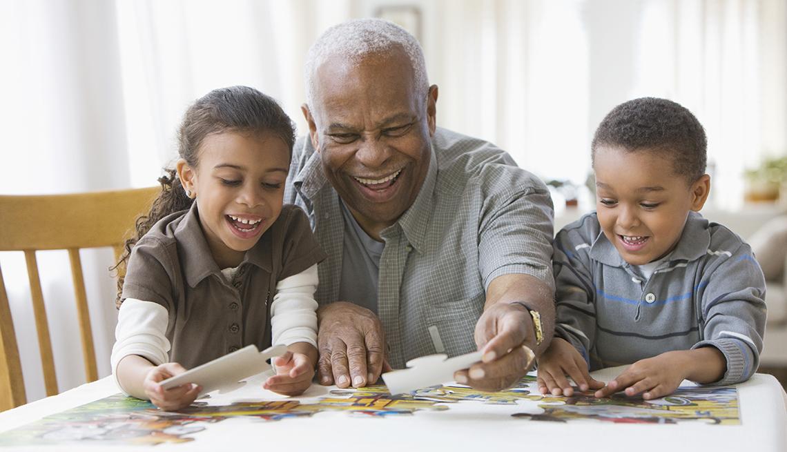 Abuelo con los y nietos construyendo un rompecabezas