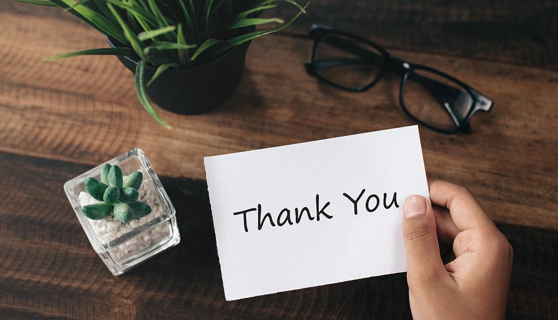 Persona sostiene una nota que dice thank you