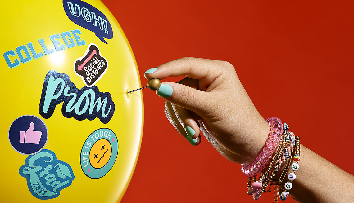 a young girls hand sticks a pin into a balloon with stickers on it that says things like college and prom and ugh